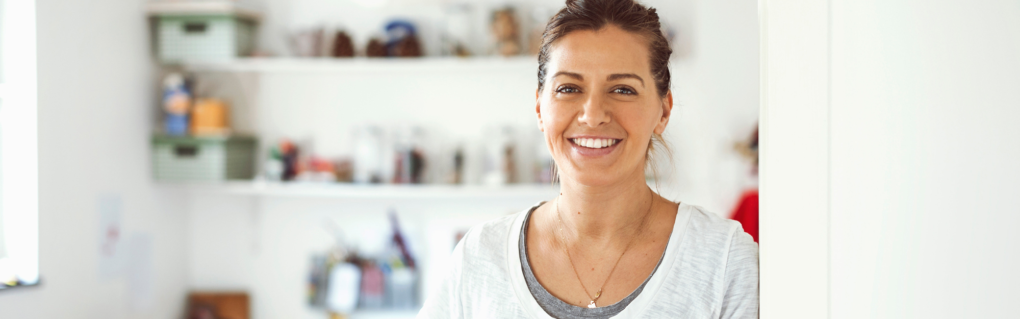 Smiling woman leaning shoulder against wall
